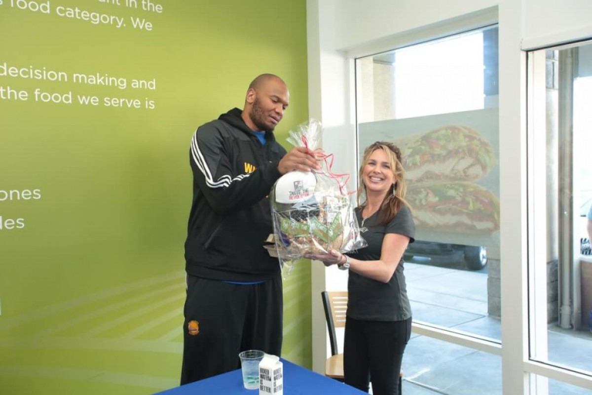 Marreese Speights receiving a gift basket